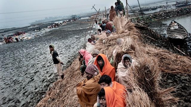 Leute in Bangladesch sitzen zusammengepfercht sind verhüllt auf einem Lehmhaufen.