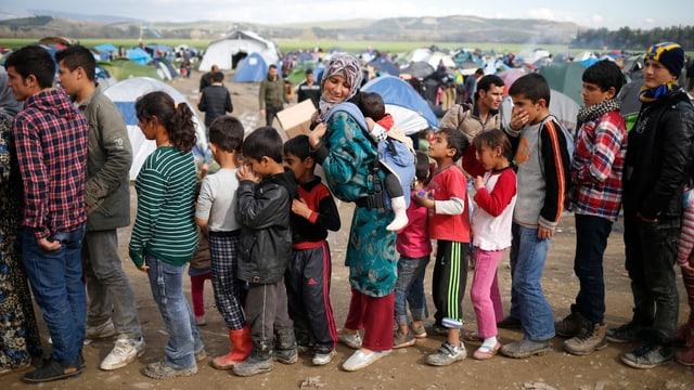 Menschen, darunter viele Kinder, stehen Schlange vor der Essensausgabe