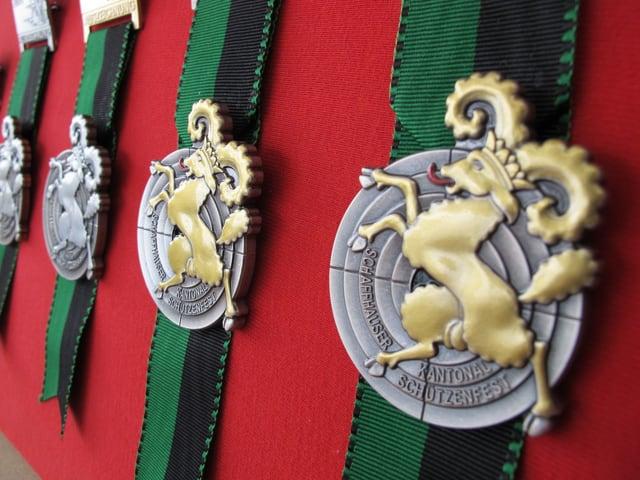 Vier Medaillen, die an einer Wand hängen.