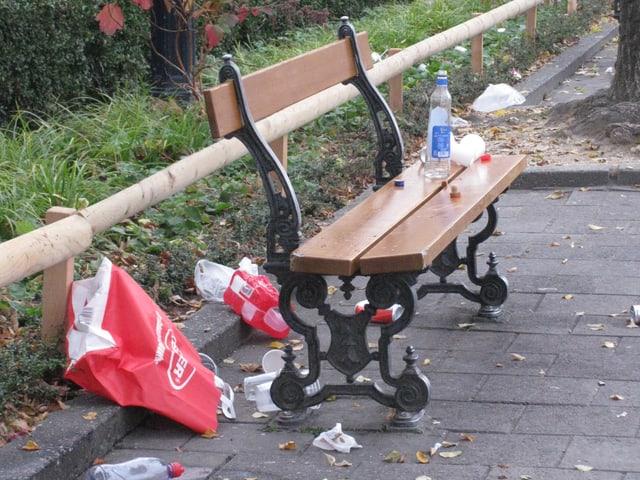 Plastikbecher und Verpackungsmaterial liegen neben einem Abfallkübel.
