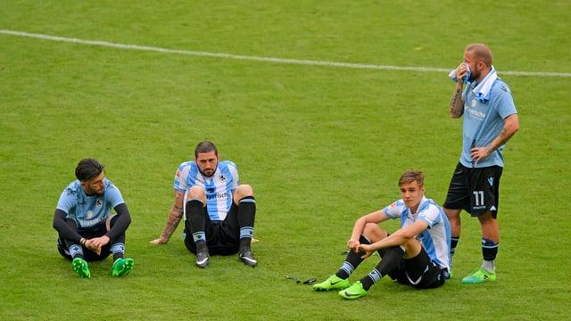 Vier Spieler vom TSV 1860 München sitzen am Boden.