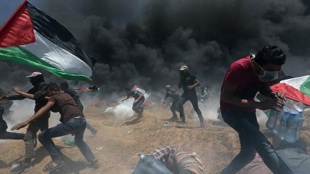 Protestierende fliehen vor Tränengas.