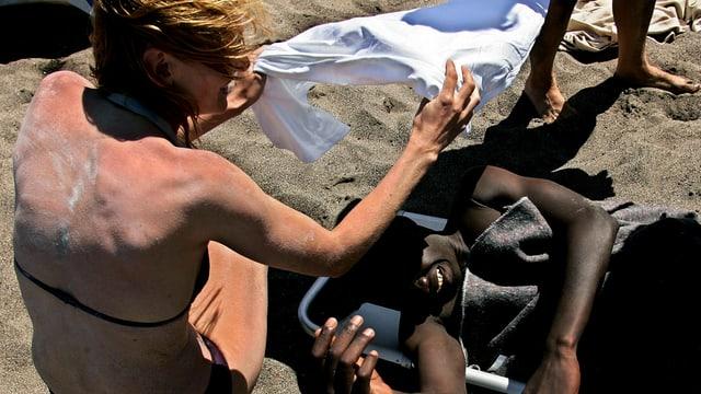 Eine hellhäutige Touristin im Bikini spendet einem dunkelhäutigen Mann auf einer Liege Schatten.