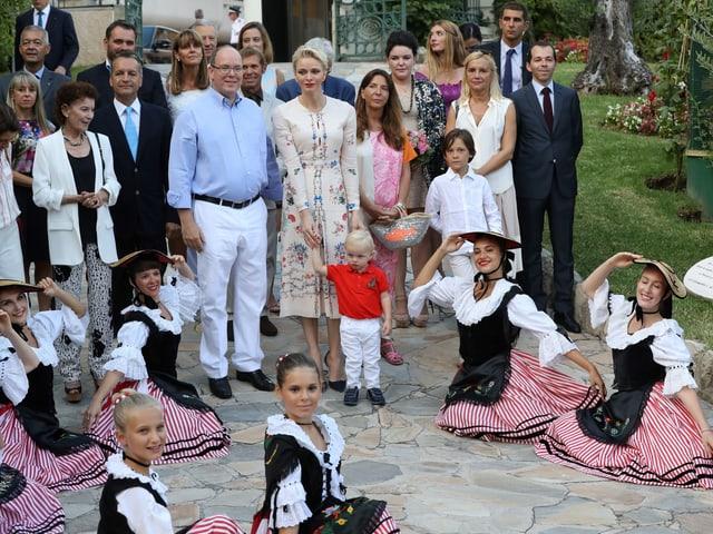 Fürst Albert, Fürstin Charlène und Prinz Jacques  posieren mit den Tänzeinnen der Folkloregruppe.