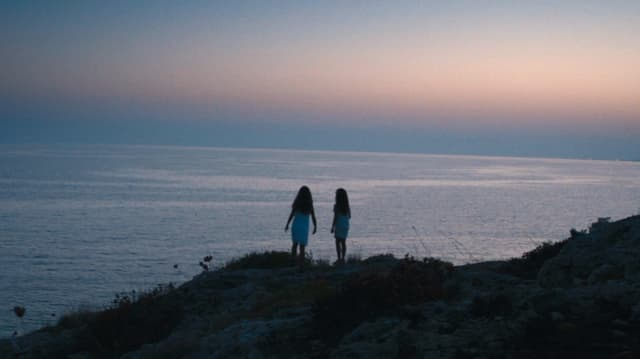 Zwei Mädchen stehen vor dem Meer.