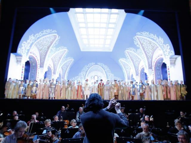 Ein Orchester mit Dirigent vor einer hell erleuchteten Bühne.