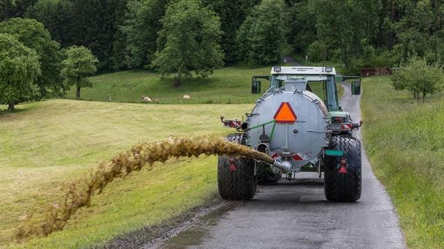 Traktor zieht einen Tank, daraus wird Gülle verspritzt.