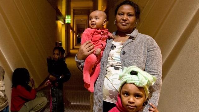 Eine Mutter steht mit ihren Kindern in einem Hotelflur