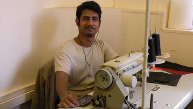 Ein Mann sitzt an einer Nähmaschine.