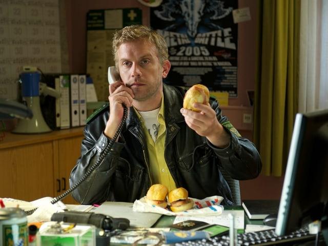 Ein Mann sitzt an einem Schreibtisch und telefoniert. In seiner linken Hand hält er ein Sandwich.