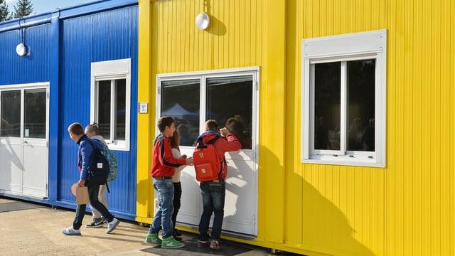 Kinder vor gelben und blauen Wohncontainern.