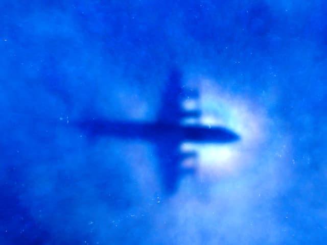Schatten eines Suchflugzeugs hinter dünnen, blauen Wolken im südindischen Ozean.