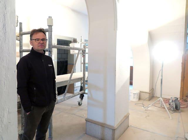 Daniel Niederberger steht zwischen Steinsäulen. Im Hintergrund ein Baustrahler und ein Baugerüst.
