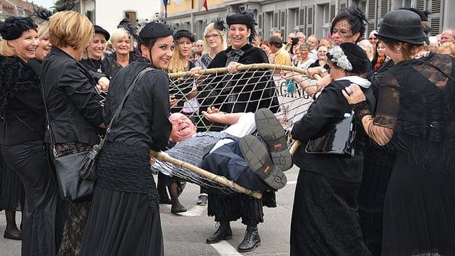 Schwarzgekleidete Frauen tragen einen Mann, der in einem Netz liegt.