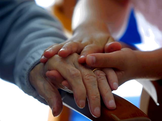 Eine Hand hält die andere.