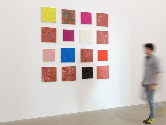 Quadratische Bilder auf einer weissen Wand im Museum. Davor läuft ein junger Mann vorbei.