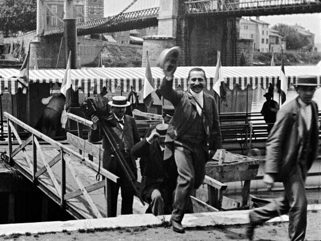 Schwarz-Weiss-Bild: Leute steigen über eine Brücke auf das Festland.