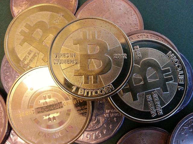 Einie Handvoll goldener Bitcoin-Münzen, die es in Wirklichkeit so gar nicht gibt.