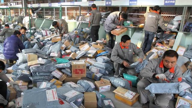 Asiatische Männer sitzen am Boden, umgeben von Hunderten von Paketen