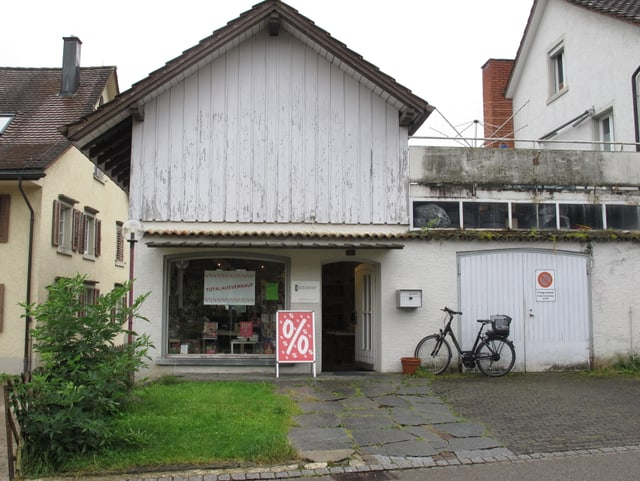 Das Haus der Buchhandlung Pfannenstil. Ein Holzhaus, weiss angestrichen.