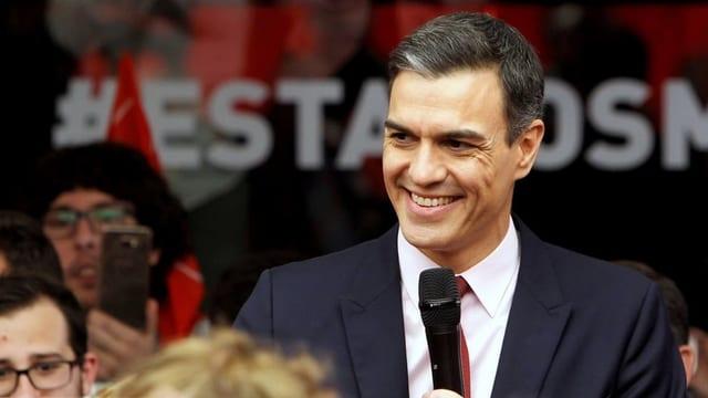 Pedro Sanchez mit dunkelblauem Anzug und weissem Hemd an einer Wahlkampfveranstaltung der Sozialisten. In der Hand hält er ein schwarzes Mikrofon.