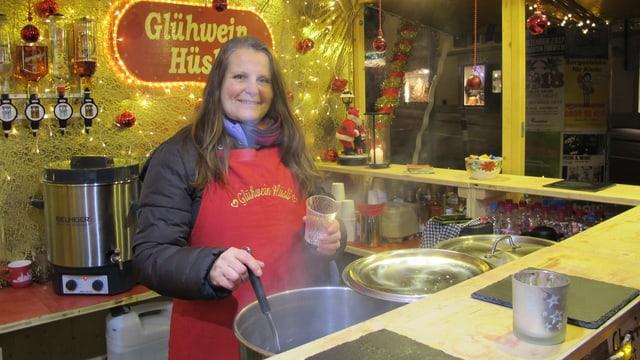 Eine Marktfahrerin schöpft Glühwein am Weihnachtsmarkt