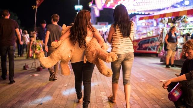 Zwei junge Frauen laufen durch ein Festgelände, eine davon hält zwei grosse Plüschtiere in den Armen.