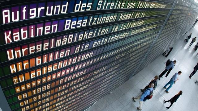 Passagiers da la Lufthansa stattan davant ina tavla che declara ch'ils sgols èn stritgads pervi da la chauma dal persunal da cabina
