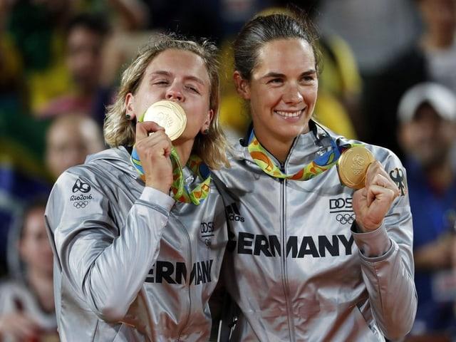 Laura Ludwig und Kira Walkenhorst küssen ihre Medaillen.