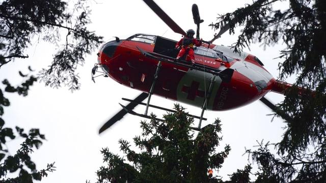 Hubschrauber mit offener Tür, Rettungssanitäter lässt Winde herunter