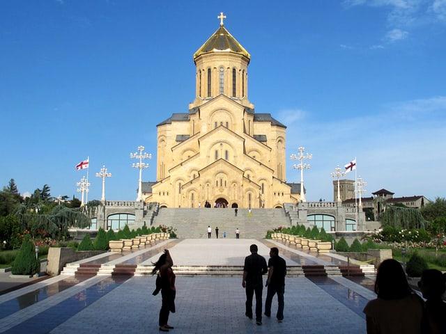 Blick auf eine Kirche, mit Menschen-Silhouetten im Vordergrund.