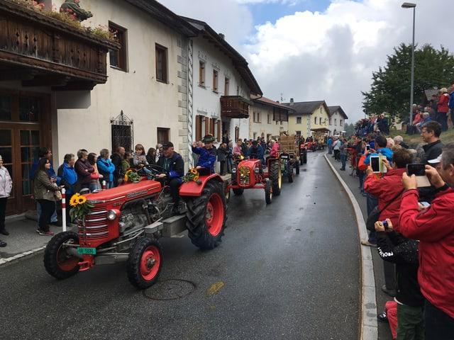 In cortegi da tractors oldtimer - dasper la via èn numerusas persunas che fotografeschan cun lur telefonins.