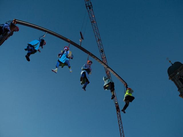 Ein Kran lässt sechs Welttheater-Darsteller, alle an einer Querstange befestigt, weit über dem Klosterplatz in Einsiedeln schweben.