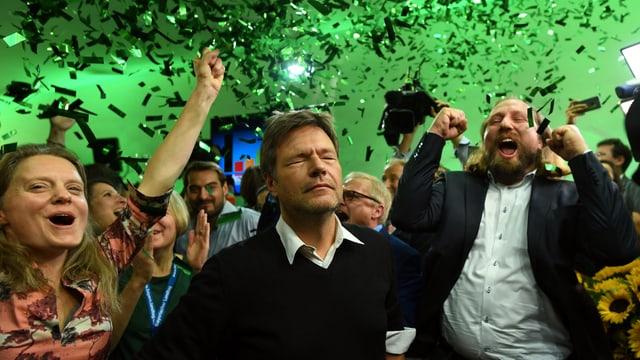 Habeck steht mit geschlossenen Augen neben jubelnden Parteikollegen, von der Decke regnen in grünem Licht grüne Glitzerschnipsel.
