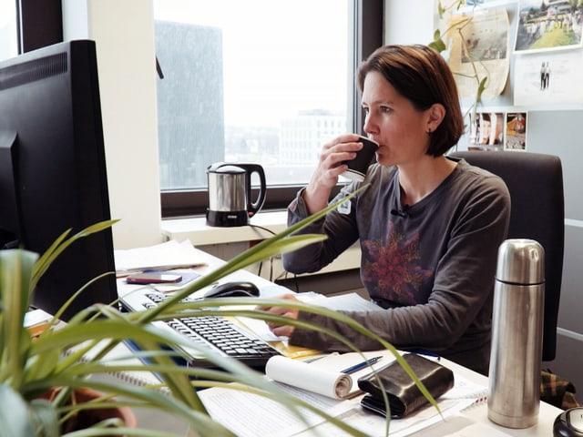 Frau am Arbeitsplatz, trinkt vor Bildschirm