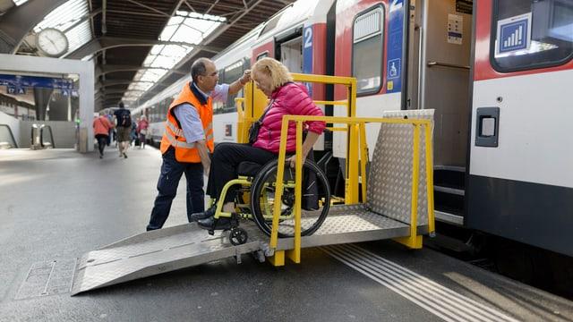 Ein SBB-Angestellter hilft einer Rollstuhlfahrerin aus dem Zug