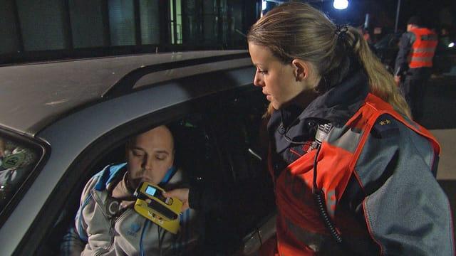 Eine Polizistin hält einem Autofahrer ein Alkoholmessgerät hin.