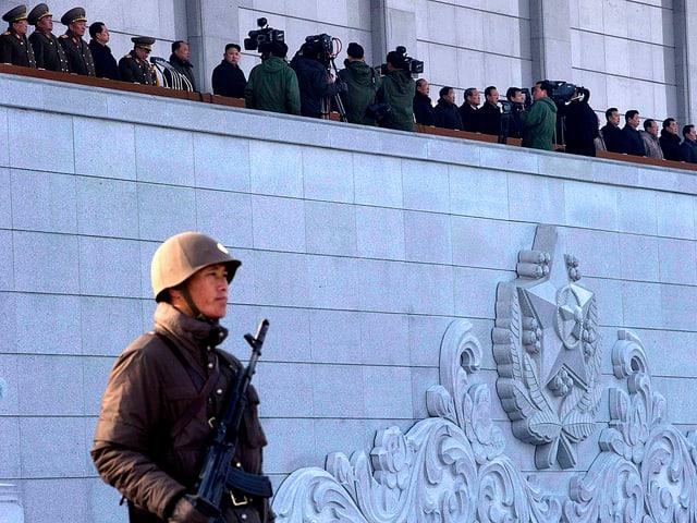 Auf dem Balkon des nordkoreanischen Kumsusan-Mausoleums stehen Würdenträger. Im Vordergrund, unter dem Balkon, ist ein nordkoreanischer Soldat zu sehen.