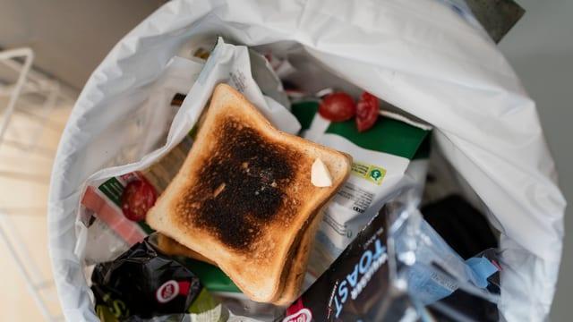 Toast und andere Lebensmittel in Mülleimer.
