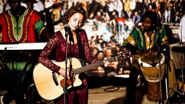 Eine Frau in einem weinroten Kleid steht vo einem Mikrofon und spielt Gitarre, links und rechts schwarze Musiker.