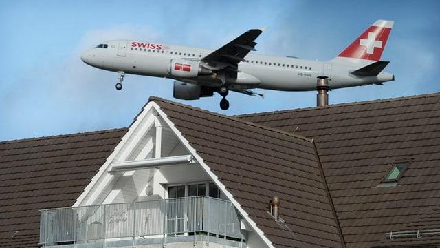 Ein Flugzeug der «Swiss» startet über einem Hausdach.