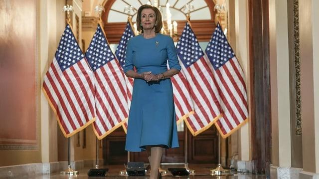 Nancy Pelosi vor mehreren US-Flaggen