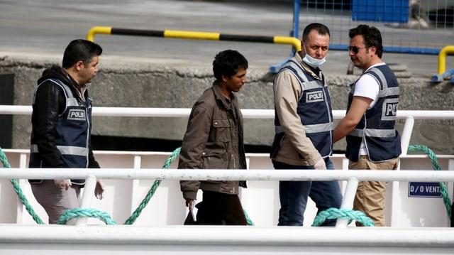 Ein Flüchtling auf einem Boot wird beim AUssteigen von Polizisten beäugt.