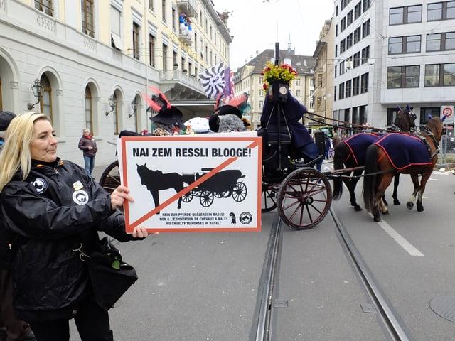 Ines Zehnder mit Protestplakat, dahinter Chaise