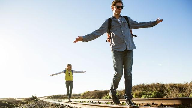 Junger Mann und junge Frau balancieren auf den Geleisen. Weite, karge Landschaft.