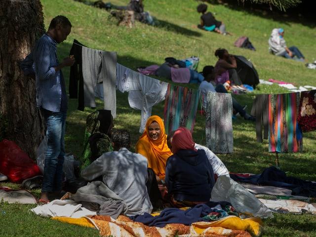 Flüchtlinge sitzen auf Decken in einem Park, dahinter Wäscheleinen