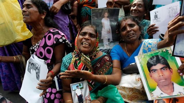 Tamilische Frauen mit Bildern von Verwandten demonstrieren.
