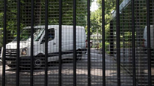 Polizeitransporter gesehen durch ein vergittertes Tor.