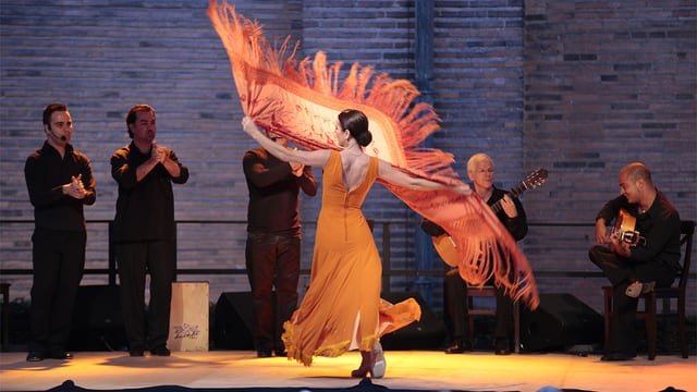 Die Flamenco-Tänzerin Bettina Castaño tanzt auf einer Bühne und wirbelt ein grosses oranges Tuch durch die Luft.