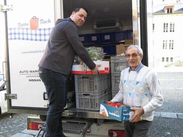 Zwei Männer laden Lebensmittel aus einem Lastwagen